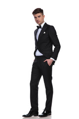 classy man in black tuxedo standing with hands in pockets