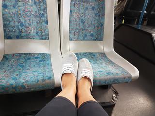 Füße auf dem Sitz im Bus
