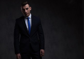portrait of handsome smart casual man in navy suit standing