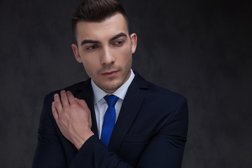 portrait of curious businessman in navy suit touching his chest
