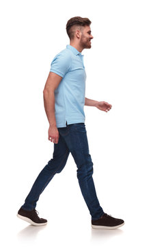 side view of casual man in blue polo shirt walking