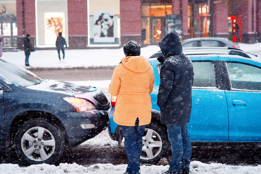 Drivers look at damaged cars after road accident in blizzard. Car crash accident on winter road with snow, unsafe distance when driving on slippery roads. Winter driving - car breakdown