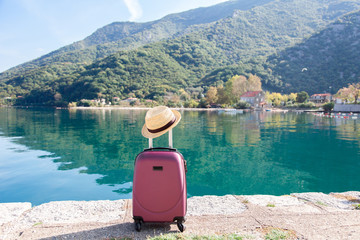 Pink suitcase with straw hat on sea beach. Concept of travel, vacation, female tourism, trip, adventure. Nature background of amazing view with blue lake, mountains, autumn landscape. Fototapete