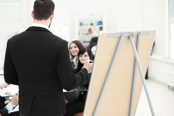 rear view. a businessman makes a presentation to employees