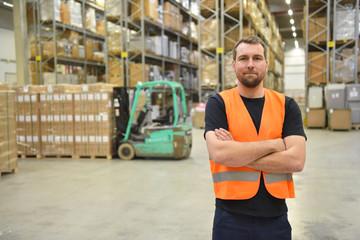 portrait of successful workers in a warehouse of a logistics company  // Mann arbeitet im Handel - Warenlagerung und Transport