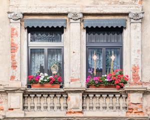 windows with geranium flower pots, old house facade detail