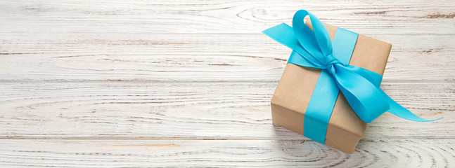 Beautiful gift box with a blue bow on the white wooden table. Top view banner with copy space for you design