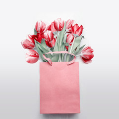 Red tulips bouquet in paper shopping bag on  light gray background. Festive spring flowers bunch. Floral gift composing. Springtime holiday , greeting or sale concept. Copy space for your design