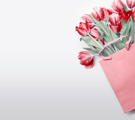 Red tulips in paper shopping bag on  light gray background. Festive spring flowers bunch. Floral gift composing. Springtime holiday , greeting or sale concept. Copy space for your design
