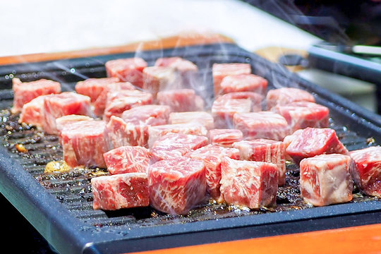 Cooking diced steak on iron hot plate. Grilling diced beef. Grill Meat Steak Barbecue.