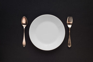White plate, spoon and fork, on a black background