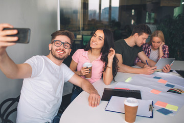 Picture of young man holding phone and take selfie with beautiful brunette. They pose and smile. Another couple sit behind them and work together. They sit in white room.