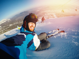 Selfie Guy sportsman goes on normal skiing on ski slope with action camera. Sunset. winter