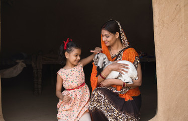 Mother and daughter with baby goat in rural house