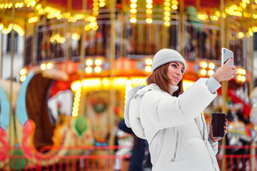 A beautiful young woman or girl in white down jacket and gray hat with coffee cup doing selfie or photographing during Christmas holidays.