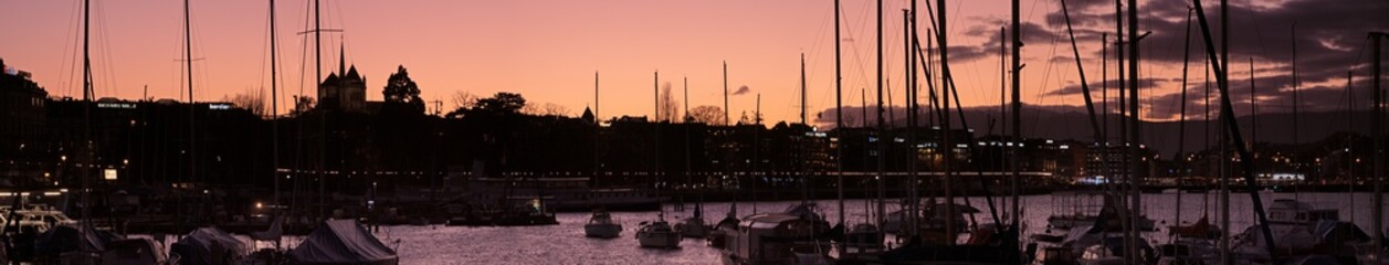 The sunsets behind a panoramic image of a boat filled lake harbor on the shores of Lake Geneva, Switzerland. The sky turns orange with the silhouette of the boats masts and boats in the foreground.