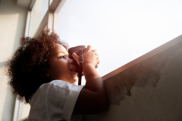 Small child little girl Curly hair holding a instant camera and taking photo near the window