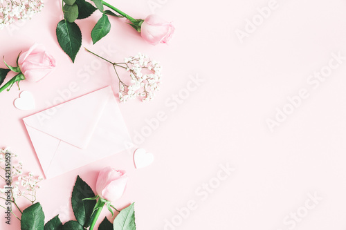 Valentine's Day composition. Pink rose flowers, envelope on pastel pink background. Valentine's day, Mother's day concept. Flat lay, top view, copy space