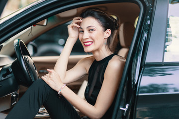 Gorgeous woman laughing, happy while sitting on the front seat i