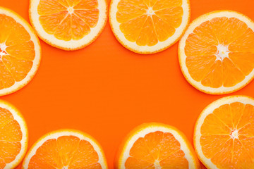 Frame from round cut slices of ripe juicy organic oranges. Top view flat lay. Vibrant color. Vitamins healthy lifestyle vegan superfoods concept. Poster banner