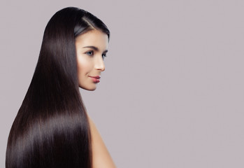 Elegant woman with straight healthy hair and clear skin on pink