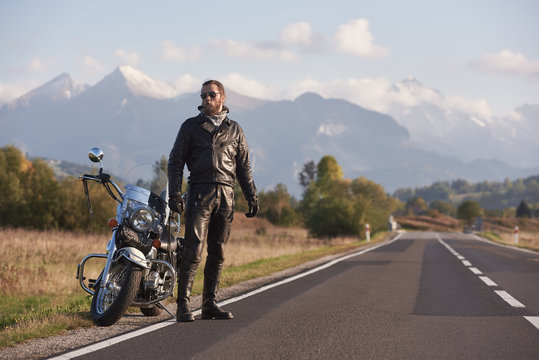 Bearded tall athletic biker in dark sunglasses, black leather clothing standing at modern powerful motorbike on background of green rural landscape, steep mountain peaks and bright sky.