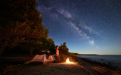 Night camping at sea coast. Female hker standing at campfire near tourist tent and forest, enjoying beautiful view of starry sky with Milky way and clear blue water. Tourism, active lifestyle concept