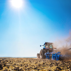 Fototapete - The tractor plows the field, cultivates the soil for sowing grain. The concept of agriculture.