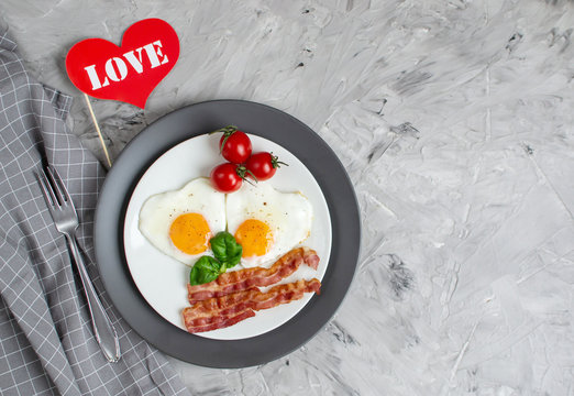 Tasty Fried Egg in the Shape of a Heart Served on a White Plate with Bacon Tomato Basil Pepper Gray Background Valentine Day Morning