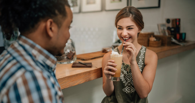 Beautiful generation z girl smiling with a iced coffee in hand at bar counter of a trendy coffee shop with mixed race guy