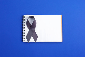 Brain cancer grey color awareness ribbon isolated on blue background