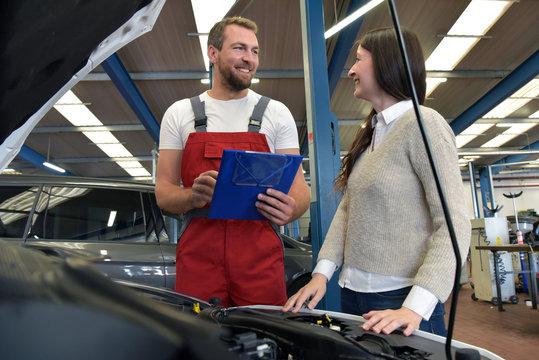 Kundendienst in der Autowerkstatt - Mechaniker und Kundin besprechen Service am PKW // Customer service in the car repair shop
