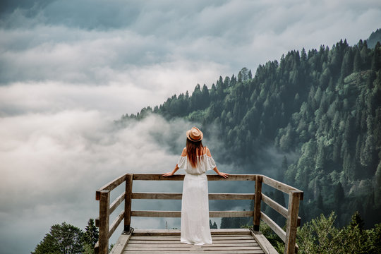 The woman with hat and white dress standing against mountains in nature