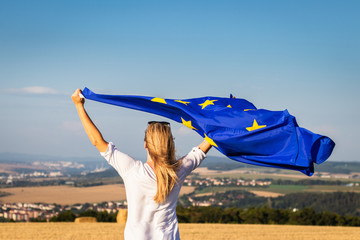 Woman holding waving european union flag outdoors