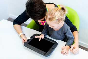 Toddler girl in child occupational therapy session doing sensory playful exercises with her therapist using digital tablet. Top view.