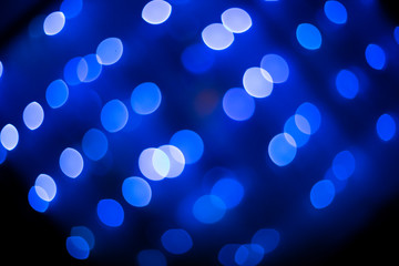 Abstract glitter defocused blue lights bokeh texture on black background