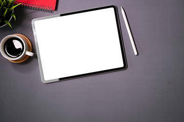 Blank screen digital touchscreen tablet on gray office desk top view and copy space