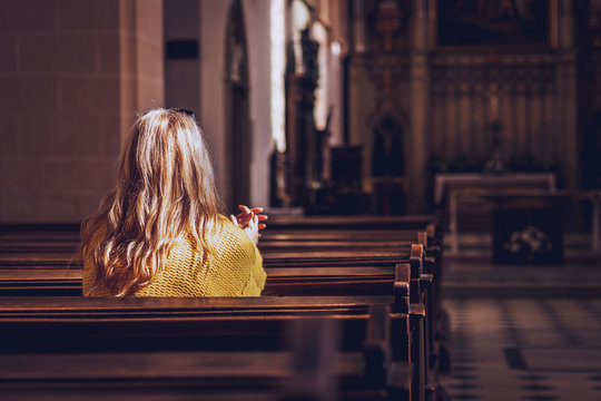 Young woman praying and meditating in church