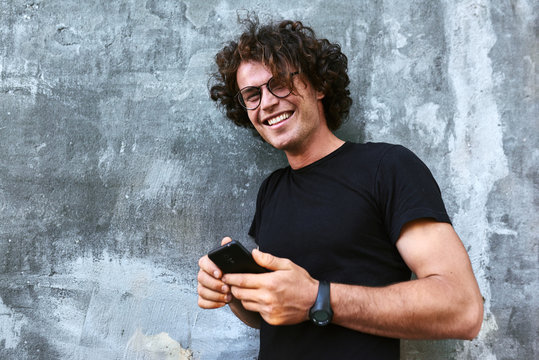 Happy smiling man standing outdoors texting on mobile phone. Young male with curly hair wears spectacles resting outside in the city browsing on his cell phone on concrete gray background.