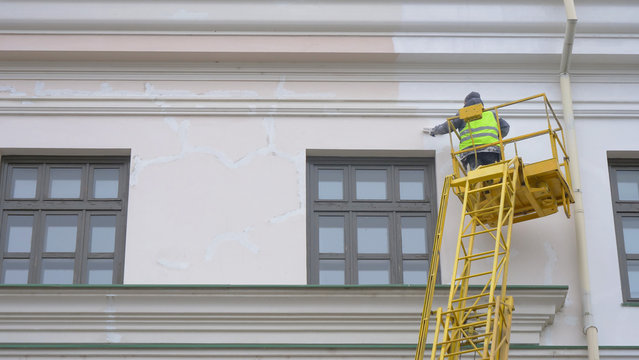 Painters standing on Aerial ladder paint the wall on construction site