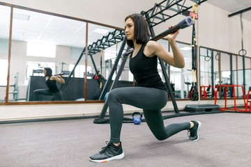 Young fitness woman exercising in modern sport gym. Fitness, sport, training, people concept.