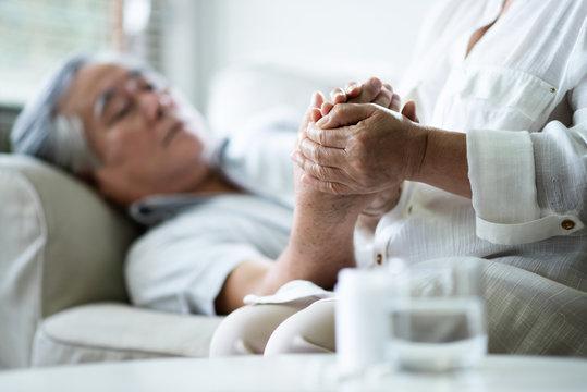 Asian Senior woman holding hands her husband.