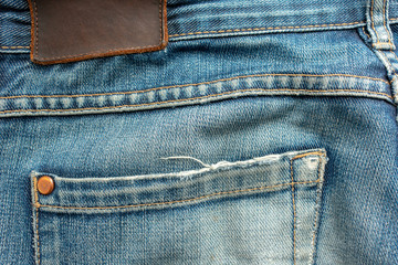 Back of old blue jeans with pocket and a leather tag. Close-up photo.