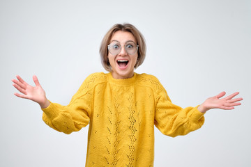 Surprised young woman in yellow sweater shouting shocked with great news