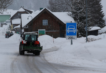 A tractor shovels snow on an icy road after heavy snowfall in Knoppen