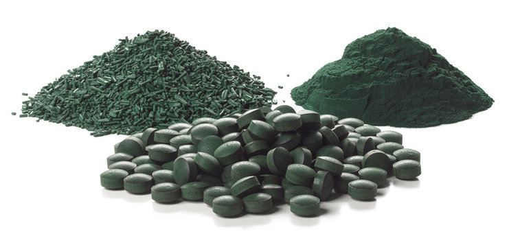 Spirulina flakes, tablets and powder over white background.