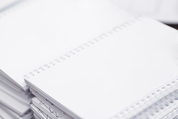 Mockup close-up of stack of white paper notebooks or notepad with white pen on the grass background
