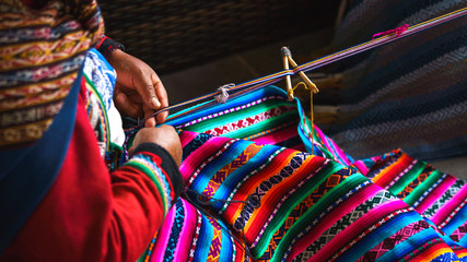 Hands of peruvian woman making alpaca wool carpet with national pattern close-up. Manufacture of wool material in Peru, Cusco. Woman dressed in colorful traditional native Peruvian closing