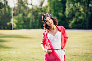 Portrait  of cute brunette girl in bandana standing in summer park. She wears white clothes, long pink shirt. She is looking to the camera.