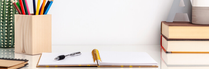 Interior in a minimalist style: a ceramic vase, books, open notebook, crayons and a ceramic cactus decoration on a white shelf against the white empty copy space wall. Panoramic photo. Concept desk